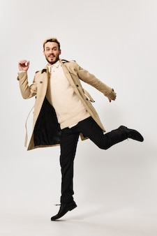 Cheerful man in coat modern style autumn fashion movement. high quality photo