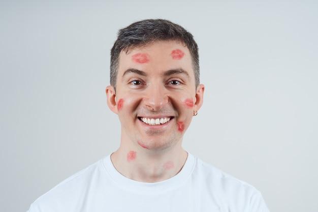 Веселый мужчина, покрытый отпечатками помады. над серой стеной. с днем святого валентина.