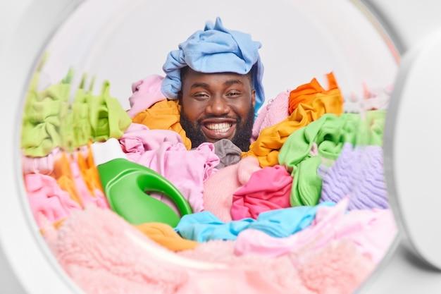 세탁 더미로 덮인 쾌활한 남자는 세탁기 안에서 재미있는 포즈를 취하며 세제를 사용하여 집에서 집안일을 합니다