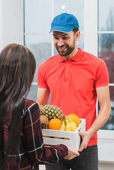 Cheerful man delivering fruits to woman