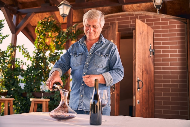 Cheerful man in a denim shirt standing on a terrace and smiling while pouring red wine into a glass decanter
