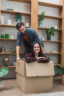 Cheerful man dragging box with woman