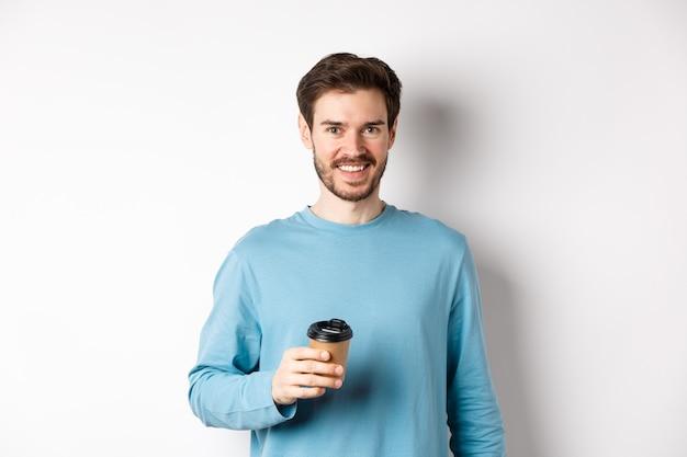 Веселый человек пьет кофе из кафе на вынос и улыбается, стоя с бумажным стаканчиком на белом фоне.