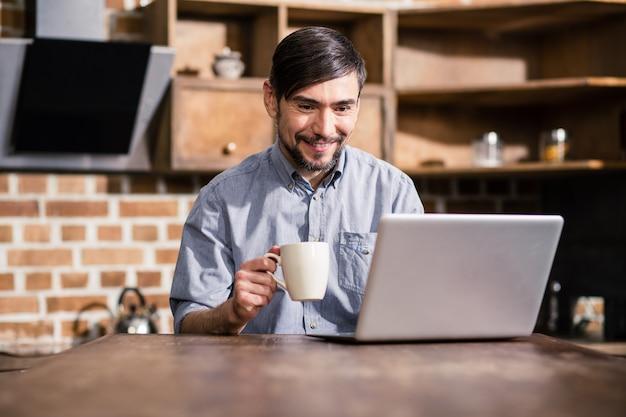 Веселый мужчина пьет кофе во время чтения новостей онлайн