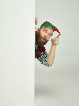 Cheerful man in elf costume pointing to something with his finger