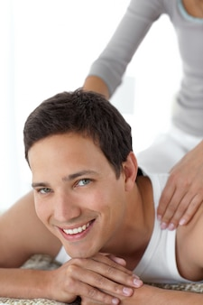 Cheerful man enjoying a back massage from his girlfriend on their bed
