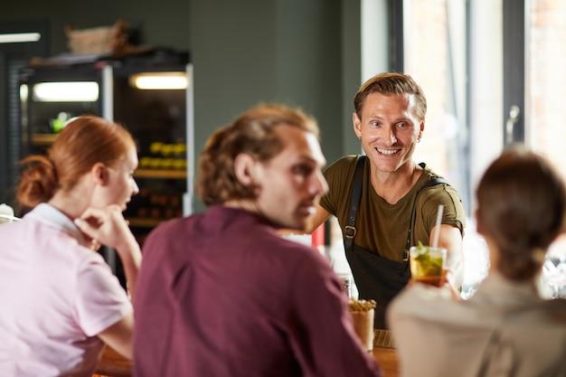 陽気な男がカフェで友達とランチを楽しんで