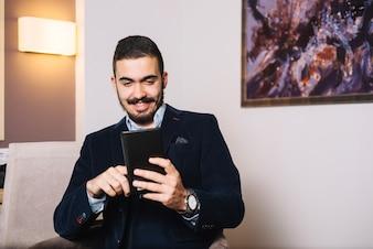 Cheerful man enjoying tablet