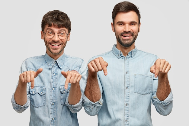Cheerful man fellows with positive expressions, point down, involved in advertisement, dressed in casual wear