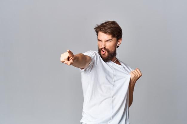 白いtシャツカジュアルウェアダンスで彼の手で身振りで示す陽気な男