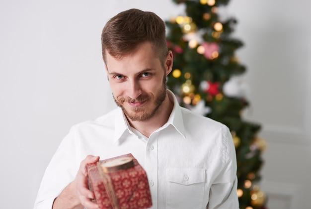 Веселый мужчина делает подарок