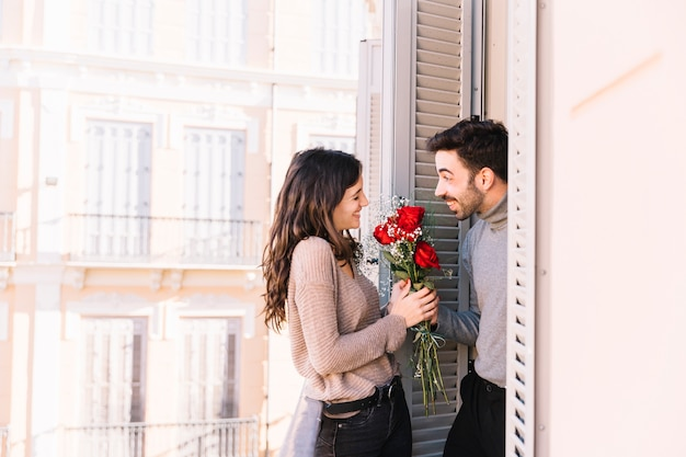 Cheerful man giving bouquet to woman