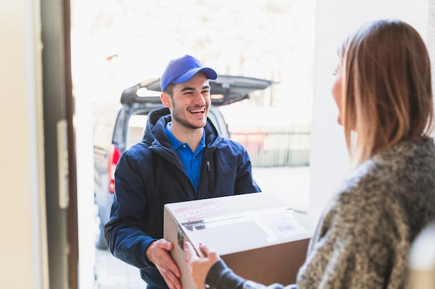 Cheerful man giving parcel to client