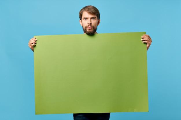 孤立した背景のマーケティングの手に陽気な男のグリーンペーパー