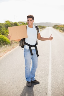 Cheerful man hitchhiking with cardboard on countryside road