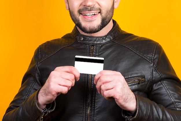 銀行カードのクローズアップを保持している陽気な男