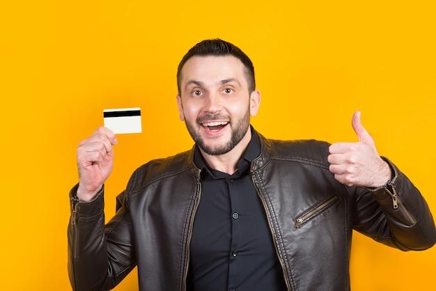 黄色の手に銀行カードを持っている陽気な男