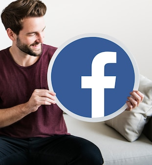 Веселый мужчина держит значок facebook