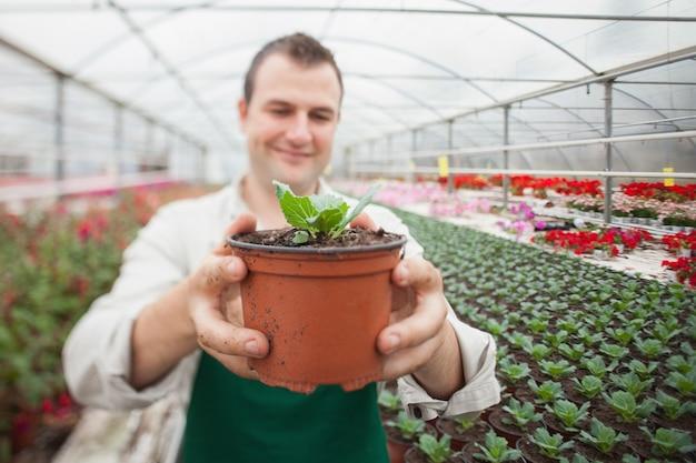 鉢植えをしている陽気な男