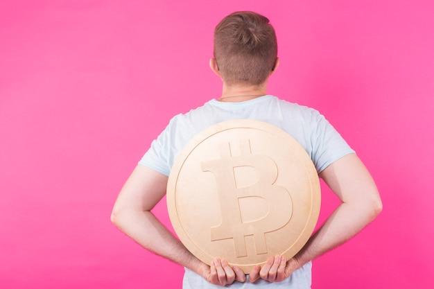 Веселый мужчина держит золотой биткойн - популярная криптовалюта, виртуальные деньги