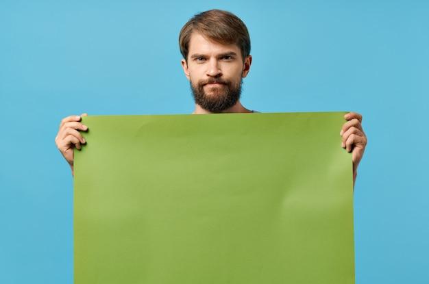 緑のモックアップポスター割引コピースペーススタジオを保持している陽気な男