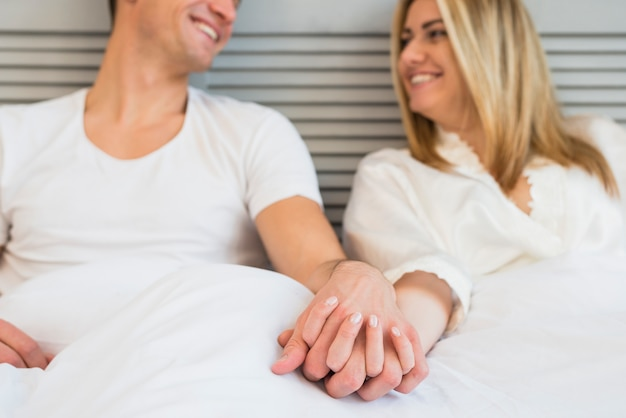 Cheerful man holding hand of young woman in bed