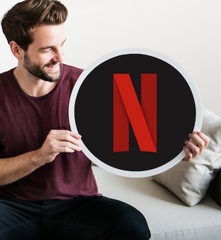 Cheerful man holding a netflix icon