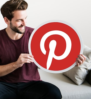 Cheerful man holding a pinterest icon