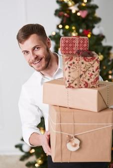贈り物のスタックを保持している陽気な男