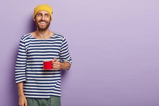 쾌활한 남자는 빨간 머그잔을 들고 기쁜 표정을 지으며 노란 모자와 줄무늬 스웨터를 입습니다.