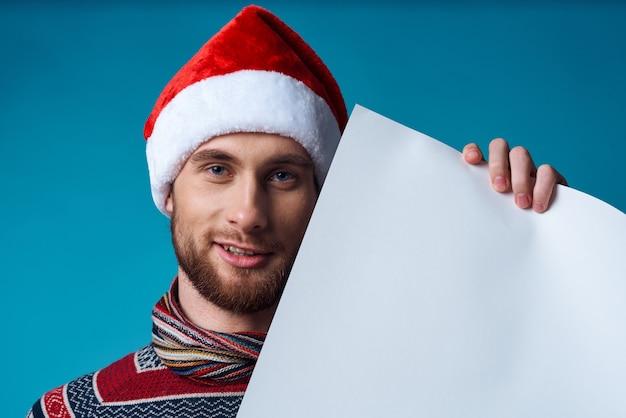 クリスマスの白いモックアップポスタースタジオポーズで陽気な男