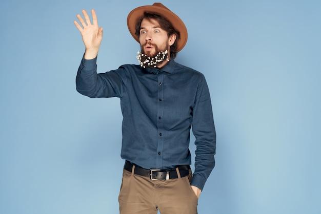 シャツを着た帽子をかぶった陽気な男は、ひげのモダンなスタイルで花をファッションします