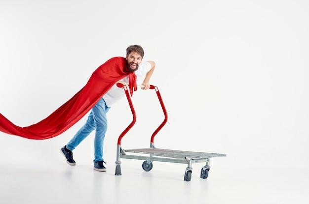 Веселый человек в красном плаще транспорта на изолированном фоне коробки