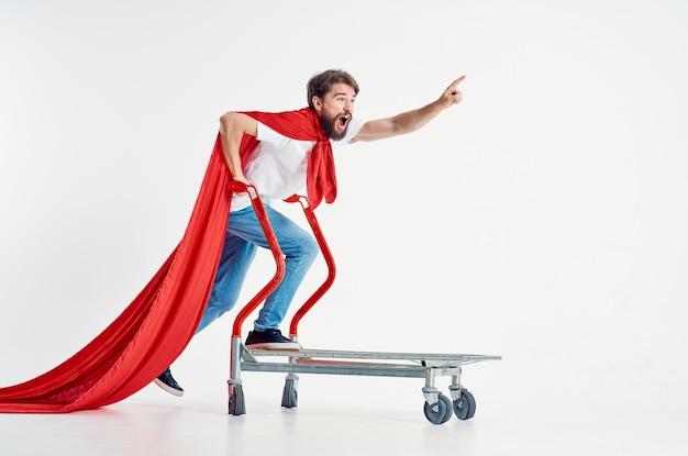 ボックスライトの背景に赤いマント輸送の陽気な男。高品質の写真