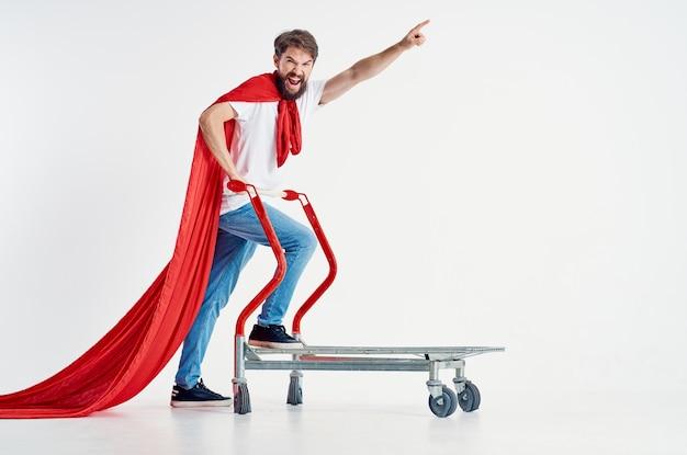 Веселый человек в красном плаще транспорта на светлом фоне коробки