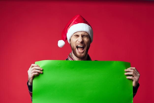 バナーの休日の赤い背景を保持しているサンタ帽子の陽気な男
