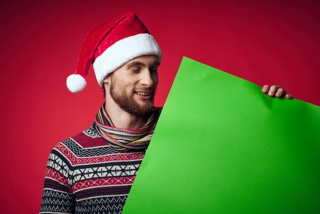 배너 휴일 스튜디오 포즈를 들고 산타 모자에 쾌활 한 남자. 고품질 사진