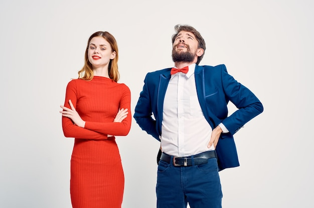赤いドレスの知人の女性の隣にスーツを着た陽気な男。高品質の写真