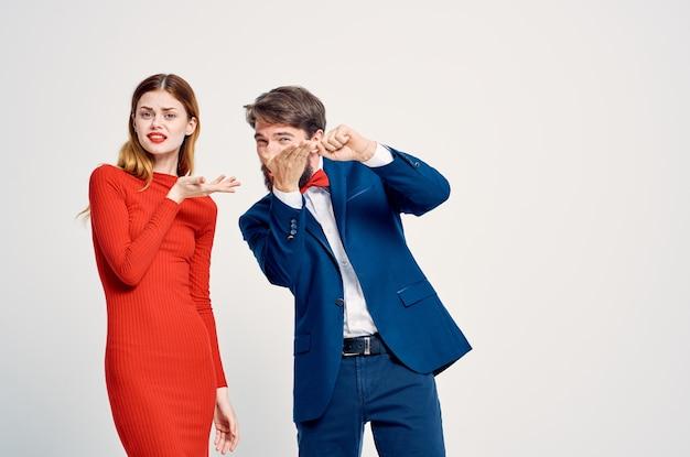 赤いドレスの知人の女性の隣にスーツを着た陽気な男