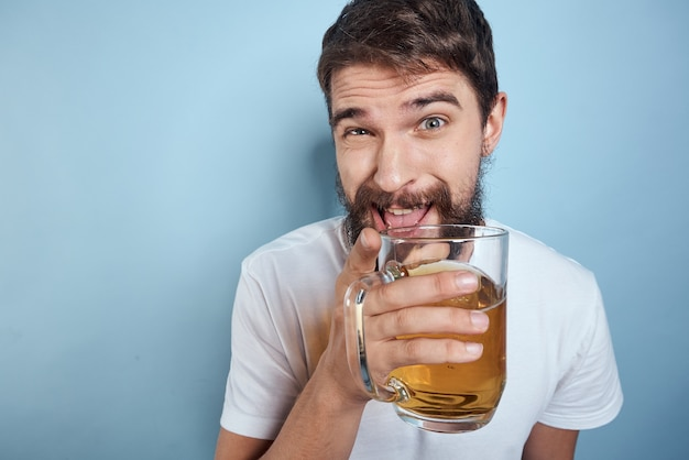 Веселый человек в белой футболке с пьяной синей кружкой пива.