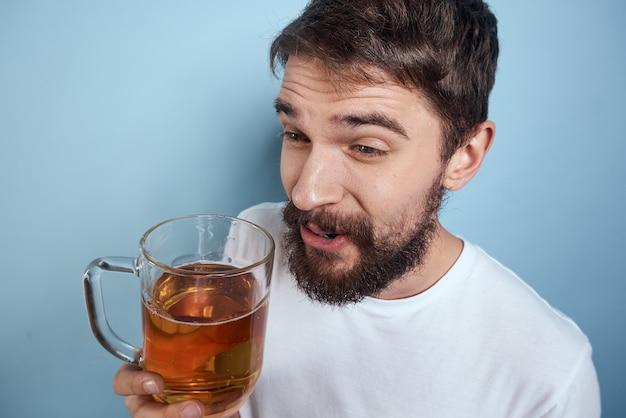 파란색 배경에 술에 취해 맥주 머그잔과 흰색 티셔츠에 쾌활 한 남자.