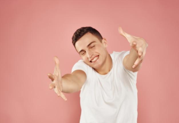 彼の手ピンクの背景で身振りで示す白いtシャツの陽気な男