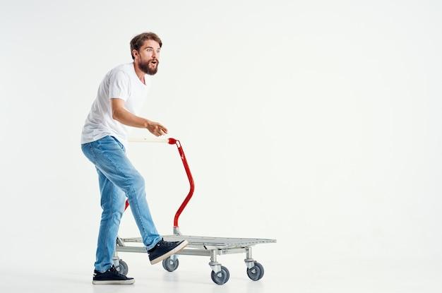 Веселый мужчина в белой футболке-транспорте в коробке на светлом фоне