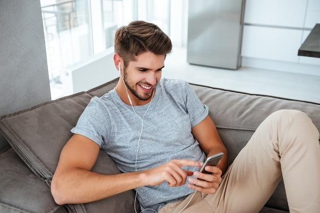 소파에 누워있는 동안 음악을 듣고 이어폰에 쾌활 한 남자. 전화로보고 채팅.