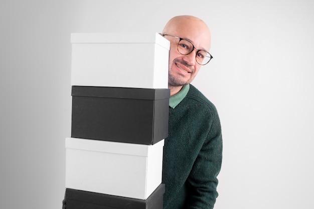 우아한 옷을 입고 쾌활 한 남자는 검은 색과 흰색 상자를 보유하고