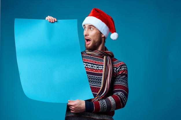 コピースペース青い背景を宣伝する新年の服の陽気な男