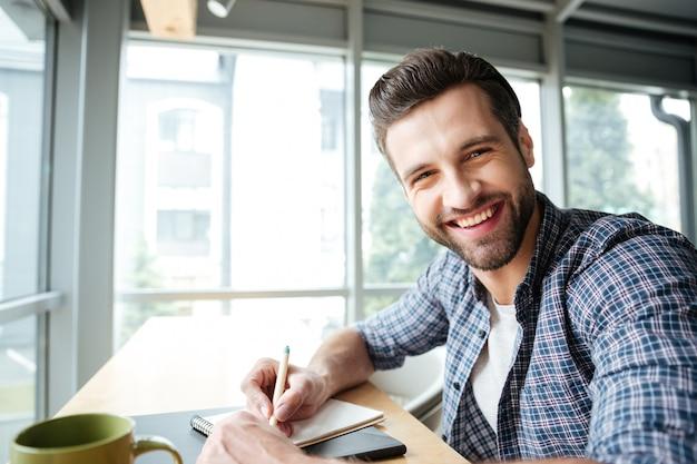 Веселый человек в офисе коворкинг во время написания заметок