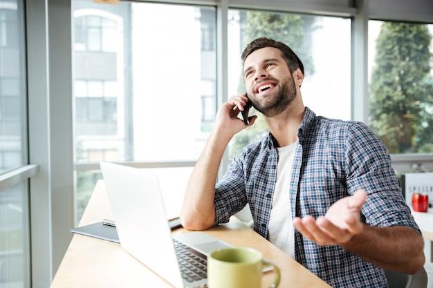 Веселый человек в офисе разговаривает по телефону