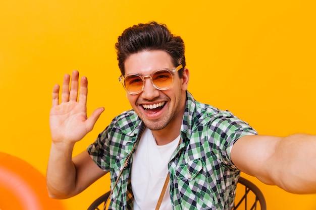주황색 안경에 쾌활한 남자는 셀카를 취하고 고립 된 공간에 그의 손바닥을 보여줍니다.