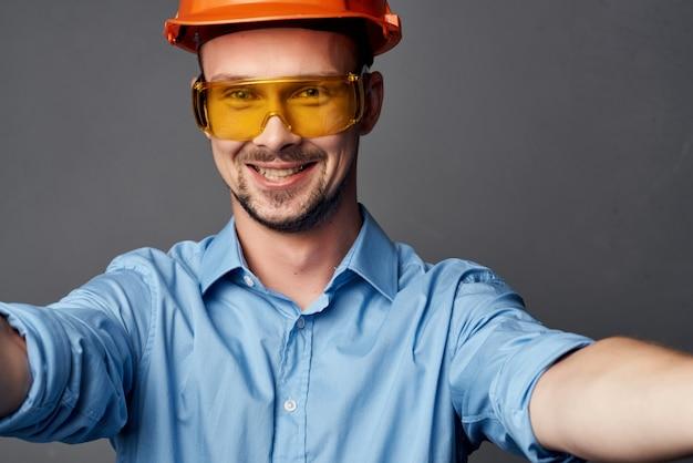 오렌지 하드 모자 건설 전문 도구에 쾌활 한 남자